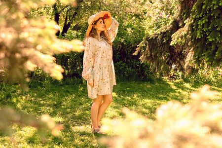 Beautiful young woman in the Park. Hat and light summer dress. Look up. Summer mood