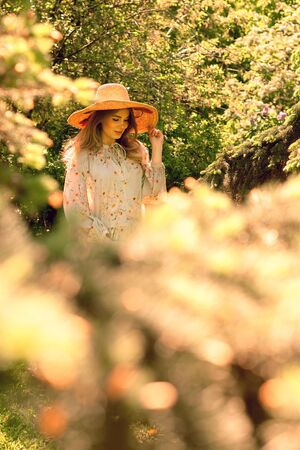 Portrait of a beautiful young woman in the forest. Hat and light summer dress. Summer mood. Walk in the Park