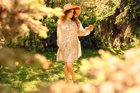 Young beautiful woman dancing in the Park. Hat and light summer dress. Summer mood