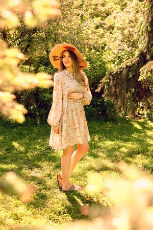 Happy young woman in the Park. Summer mood. Hat and light summer dress