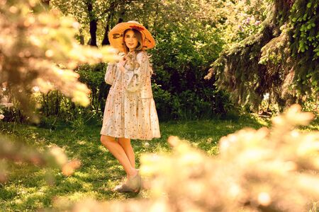 Beautiful young woman posing in the Park. Summer mood. Hat and light summer dress