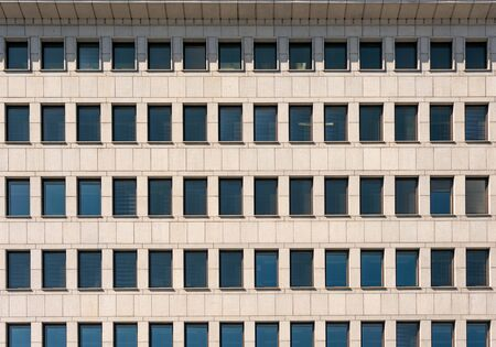 The facade of the modern building with rectangular Windows and cornice. Direct forms, laconic architecture