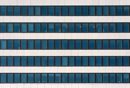 A fragment of the facade of a modern office building. Windows and light decorative stone. Organization of workplaces