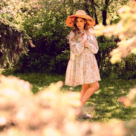 Beautiful young woman posing in the Park. Summer dress and hat. Forest and glade.