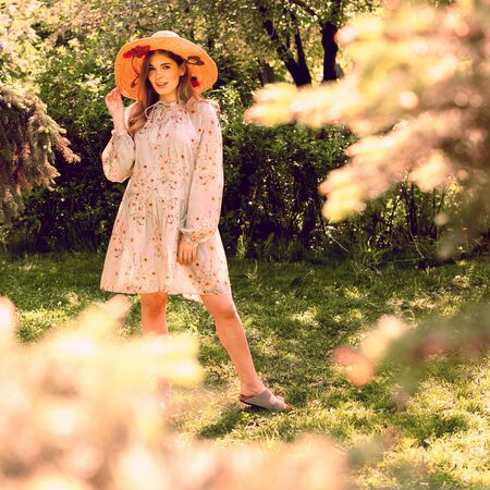 Beautiful young woman posing in the Park. Hat and light summer dress. Clearing in the forest. Reklamní fotografie