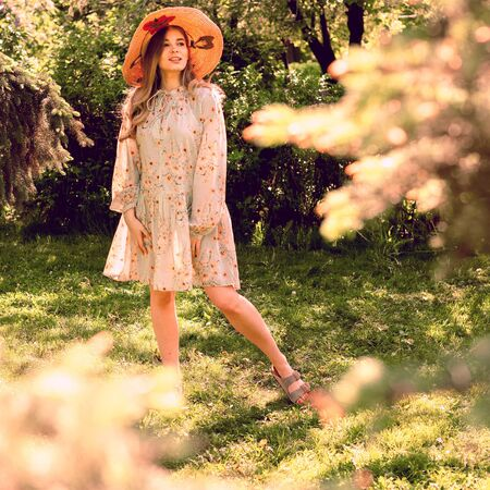 Beautiful young woman in the Park. Hat and light summer dress. Clearing in the forest. Reklamní fotografie