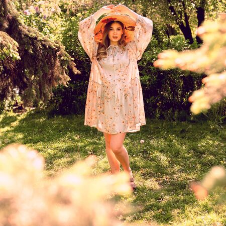Beautiful young woman in the forest. Hat and light summer dress. Summer mood. Reklamní fotografie
