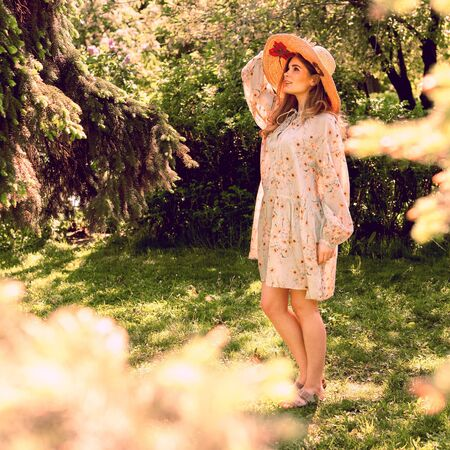 Beautiful young woman in the Park. Hat and light summer dress. Look up. Summer mood.