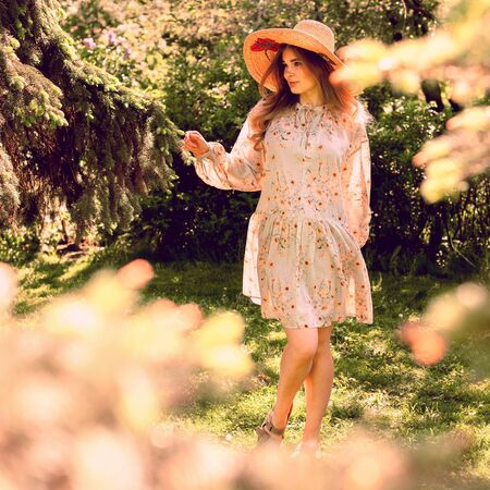 Young beautiful woman dancing in the Park. Hat and light summer dress. Summer mood. Reklamní fotografie