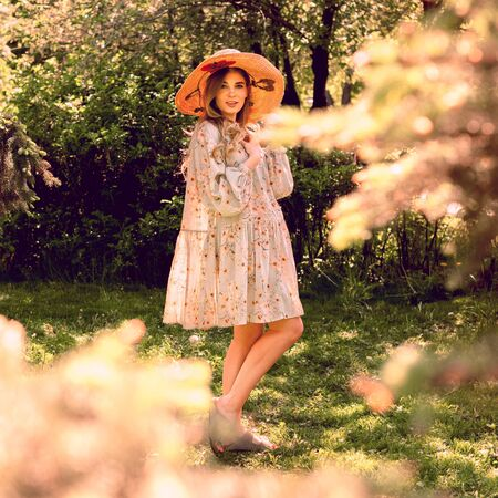 Beautiful young woman posing in the Park. Summer mood. Hat and light summer dress. Reklamní fotografie