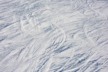 Lots of ski tracks in the snow. Skiing on the ski slope. Background vacation in the mountains