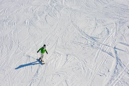 Snowboarder on the ski slope. Footprints in the snow. Winter vacation