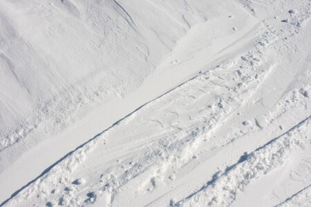 Snow close-up. Ski slope with traces of skis. Winter background