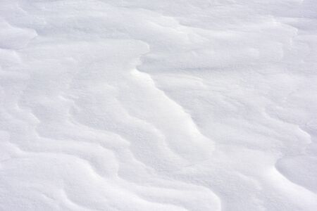 Snow close-up. The Alpine slope is in the wind. Winter background
