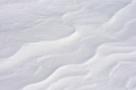 Snow close-up. Wavy texture. The Alpine slope is in the wind. Winter background