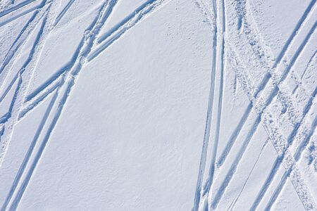 Top view of the ski tracks on the snow slope tracks. Winter sports background