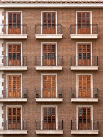 Beautiful facade of a brick building with balconies. Classic European style with shutters