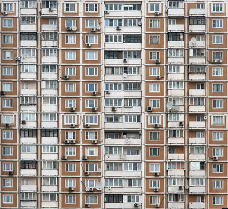 The facade of a multi-storey residential building with many windows. Old houses made of precast concrete. Cheap apartments