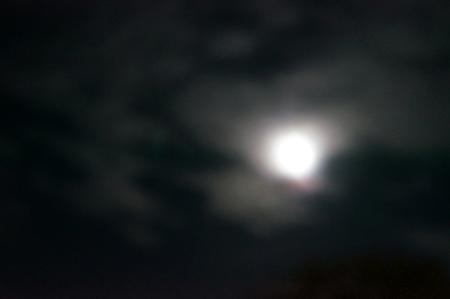 purposely: Full moon among the clouds in the night sky, purposely blurred abstract bacground
