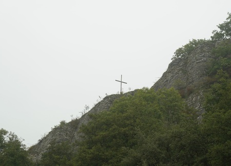 liege: Foggy cold morning and worship cross on the mountain in Comblain-au-Pont, Liege province, Belgium