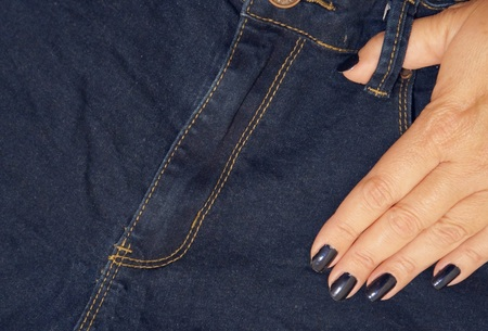 Jeans and a female fingers with blue nail polish Stock Photo