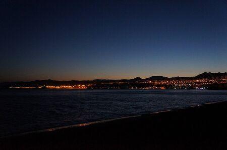 Skyline of Eilat at night: coastline, beach, hotels, promenade, mountains and bay Stock Photo