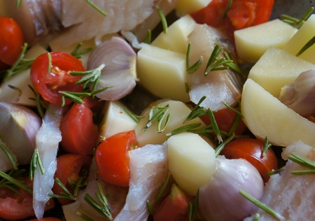 Slices of precooked raw fish and vegetables with herbs