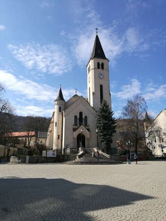 A church with a clock tower in front of a building in Tokaj 写真素材