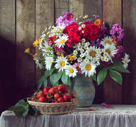 Still life in rustic style with a bouquet of garden flowers and a basket of strawberries.