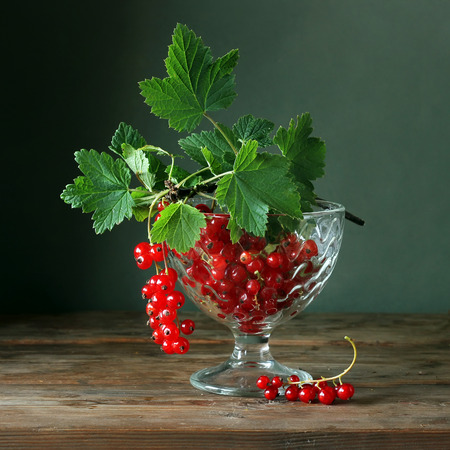 Still life with red currants in a glass vase on the table against a green background.