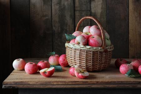 Appelen in de mand op een houten tafel. Stilleven met appels in een rustieke stijl.