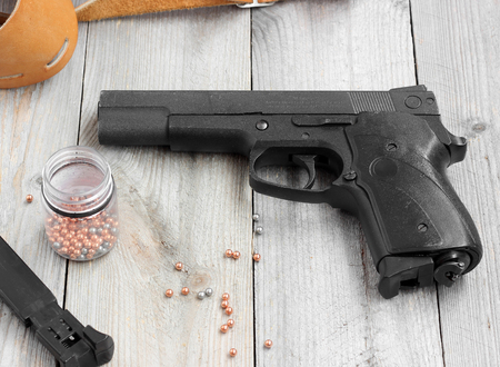 pneumatic: Pneumatic (gas) gun, magazine, holster and balls for shooting at a wooden table.