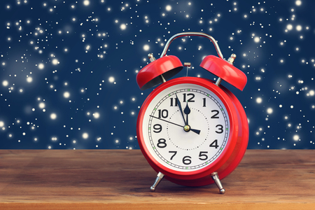 midday: Red retro alarm clock at twelve oclock amid flying snow. Midnight, midday. Minutes about New year.