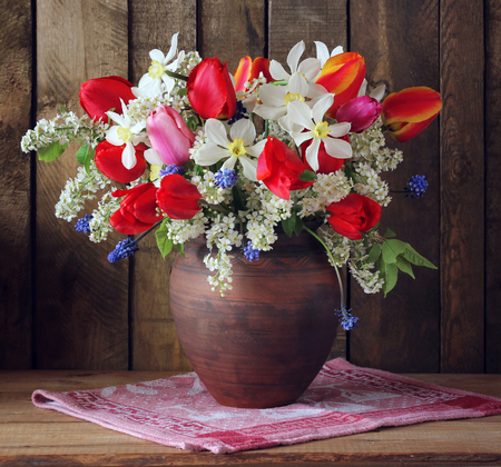 spring bouquet of daffodils and tulips in a clay jug. still life with a bouquet in rustic style.