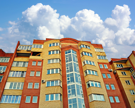 advertizing: New multystoried apartment house from a yellow and red brick with double-glazed windows against the sky with clouds.
