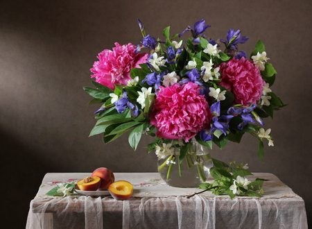 Bouquet Of Flowers In A Vase And Peaches Are On The Table With