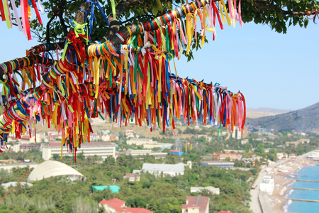 sudak: Colored ribbons on the tree making a wish on a cliff against the sea and the city.
