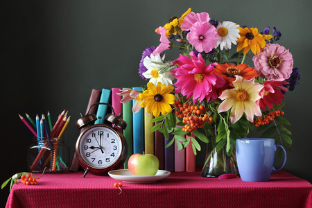 Back to school. September 1, knowledge day. The teachers day. Textbooks and bouquet, alarm clock, Apple and colored pencils on the table. Still life.