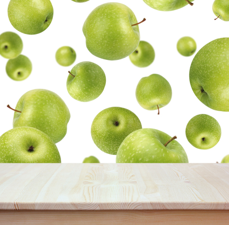Empty of wood table top on the background of flying green apples. For montage product display or design key visual layout.