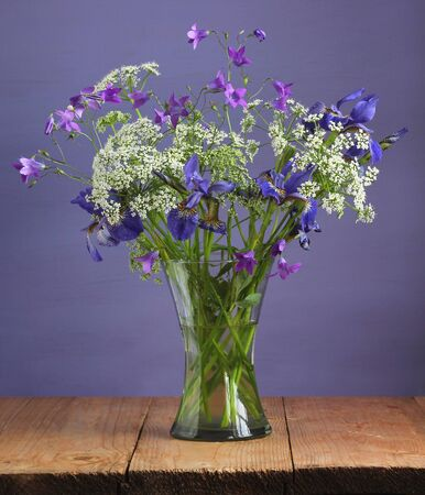 summer bouquet with purple and white flowers in a glass vase.