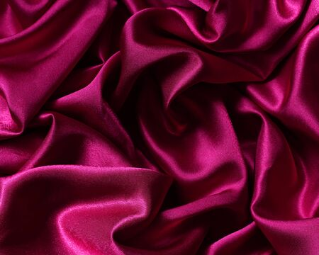 chic red satin material in a crease. luxurious fabric for the background. space for text.
