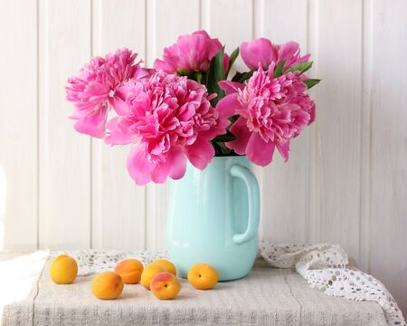 pink peonies and apricots. bouquet of garden flowers in a jug and fruit on a table against a white plank wall.