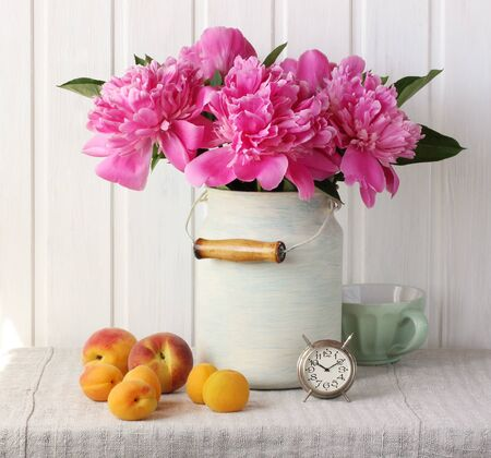 still life with a bouquet of pink peonies, peaches and apricots. bouquet of garden flowers in a can, an alarm clock and fruit on the table.