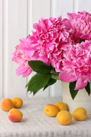 pink peonies and apricots. bouquet of garden flowers and fruit on the table. Stock Photo