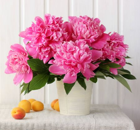 pink peonies and apricots. lush bouquet of garden flowers and fruit on the table. selective focus. Reklamní fotografie