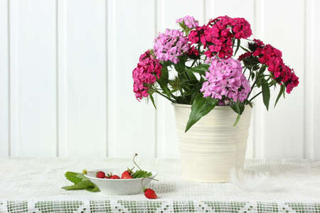 bouquet with Turkish carnation and garden strawberries on the table. light still life in rustic style. Stock Photo