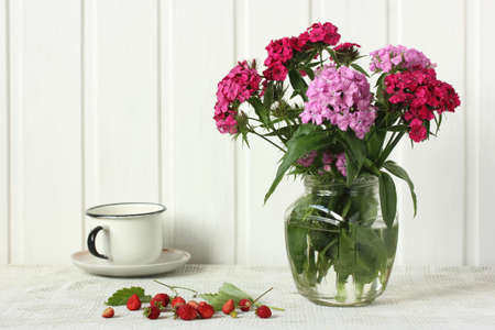 bouquet with Turkish cloves and garden strawberries on the table. light still life in rustic style.