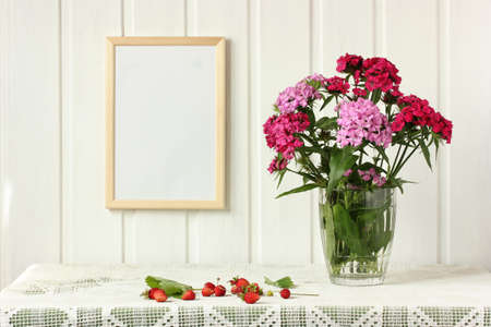 empty frame on the wall, bouquet of Turkish carnations and garden strawberries on the table. light still life in rustic style. mockup, scene creator.  Stock Photo