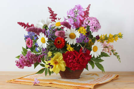 summer bouquet of garden flowers on a table against a white wall. roses, daisies and other flowers on a light background. Stock Photo