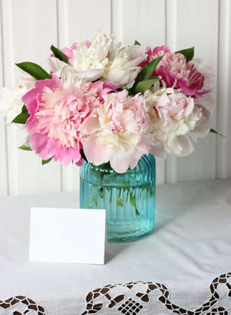 mockup, scene creator. pink peonies in a glass vase and an empty card on a lace tablecloth table. bouquet of garden flowers. Stock Photo